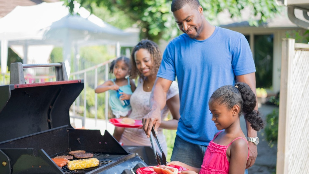 A family grilling out on their propane powered outdoor kitchen