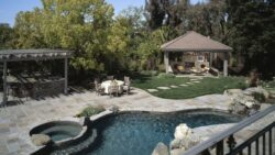 A beautiful backyard pool with grilling area and a fireplace powered by propane
